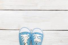 Behandla som ett barn lite blåttgymnastikskor på en vit träbakgrund Fotografering för Bildbyråer