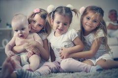 Behandla som ett barn lite brodern med systrar poserar till kameran Royaltyfria Bilder