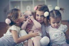 Behandla som ett barn lite brodern poserar till kameran med små systrar Arkivbild