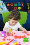 Behandla som ett barn lite flickabarnet som spelar plasticine på tabellen Royaltyfria Bilder