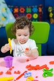 Behandla som ett barn lite flickabarnet som spelar plasticine på tabellen Arkivbild