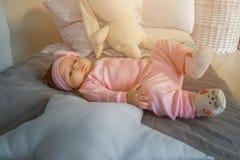 Behandla som ett barn lite flickalögner på en säng fotografering för bildbyråer