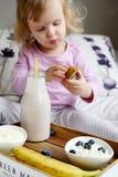 Behandla som ett barn lite flickan som äter den sunda frukosten Arkivbild