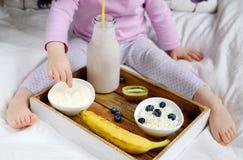 Behandla som ett barn lite flickan som äter den sunda frukosten Fotografering för Bildbyråer