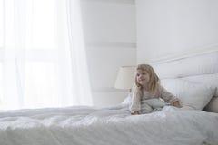 Behandla som ett barn lite flickan får upp i morgonen med leende Fotografering för Bildbyråer