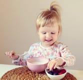 Behandla som ett barn lite flickan som hemma äter den sunda frukosten, bär och yoghurt Arkivfoton