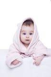 Behandla som ett barn lite flickan med blåa ögon i den rosa badrocken som ligger på henne, är arkivfoto
