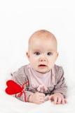 Behandla som ett barn lite flickan med röd hjärta på en pinne Royaltyfri Foto