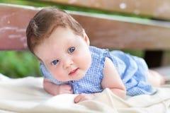 Behandla som ett barn lite flickan på hennes mage på en trädgårds- bänk Royaltyfri Fotografi