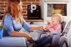 Behandla som ett barn lite flickan sitter i hög stol och gör det första försöket att äta med en sked Arkivfoton