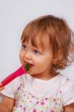 Behandla som ett barn lite flickan som äter broccoli med, dela sig Arkivfoton