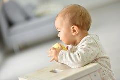 Behandla som ett barn lite flickan som äter det gula äpplet Royaltyfri Bild