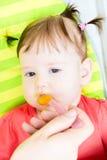 Behandla som ett barn lite flickan som äter en grönsakpuré i a Royaltyfri Bild