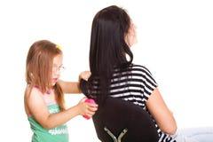 Behandla som ett barn lite flickan som borstar henne moderhår Arkivbild