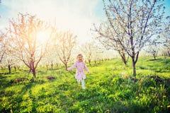 Behandla som ett barn lite flickan som kör mellan blomningträd på solnedgången Ar Royaltyfri Foto
