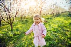 Behandla som ett barn lite flickan som kör mellan blomningträd på solnedgången Ar Arkivfoto