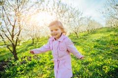 Behandla som ett barn lite flickan som kör mellan blomningträd på solnedgången Ar Arkivbild