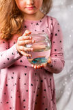 Behandla som ett barn lite flickan som rymmer en fishbowl med en blå fisk Omsorgconce Fotografering för Bildbyråer