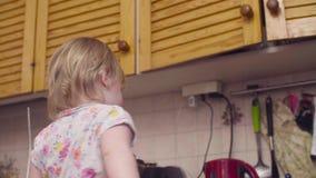 Behandla som ett barn lite flickan som spelar i köket lager videofilmer