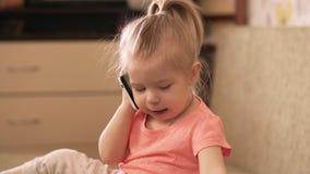 Behandla som ett barn lite flickan som spelar med den hemmastadda telefonen skott 4k lager videofilmer