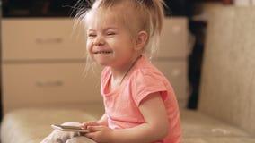 Behandla som ett barn lite flickan som spelar med den hemmastadda telefonen UHD-skott stock video