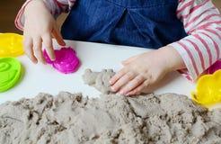Behandla som ett barn lite flickan som spelar med kinetisk sand Royaltyfri Foto