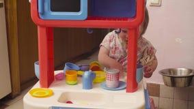 Behandla som ett barn lite flickan som spelar med vatten arkivfilmer
