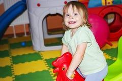 Behandla som ett barn lite flickan spelar i underhållningmitt Lyckligt barn med leksaker Fotografering för Bildbyråer