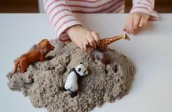 Behandla som ett barn lite flickan som spelar med kinetisk sand Royaltyfri Bild