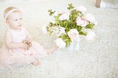 Behandla som ett barn lite flickasammanträde på en matta med halsbandet och blomman in arkivfoto