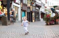 Behandla som ett barn lite flickaspring i en härlig gata Fotografering för Bildbyråer