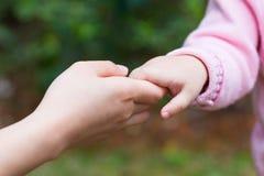 Behandla som ett barn lite hållande moderns hand Royaltyfria Foton