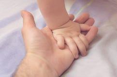 Behandla som ett barn lite handen i hand för fader` s Arkivfoto