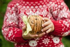 Behandla som ett barn lite i hållande kakor för jultröja med bandet royaltyfri foto