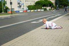 Behandla som ett barn lite i vit kläder som kryper fram vägen Arkivfoto