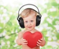 Behandla som ett barn lite med hörlurar Arkivfoton
