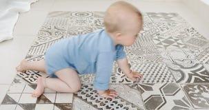Behandla som ett barn lite pojkekrypningen på golv hemma lager videofilmer