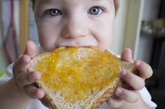 Behandla som ett barn lite pojken som äter persikadriftstopprostat bröd Arkivbilder