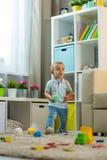 Behandla som ett barn lite pojken hemma i ett rum i inre Arkivfoto
