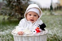 Behandla som ett barn lite pojken i en korg som rymmer den stack snögubben Royaltyfria Bilder