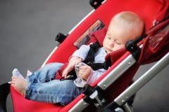 Behandla som ett barn lite pojken i sittvagn Arkivfoton