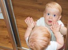 Behandla som ett barn lite pojken i spegelreflexion Arkivfoto