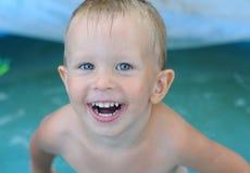Behandla som ett barn lite pojken i vattenpölen Arkivfoto