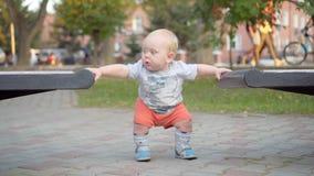 Behandla som ett barn lite pojken lär att promenera bänken I parkera utomhus- Fotografering för Bildbyråer