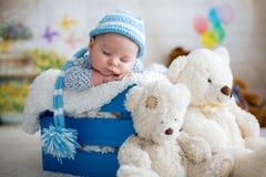 Behandla som ett barn lite pojken med den stack hatten som sover med den gulliga nallebjörnen Arkivfoto