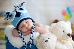 Behandla som ett barn lite pojken med den stack hatten som sover med den gulliga nallebjörnen Royaltyfri Fotografi