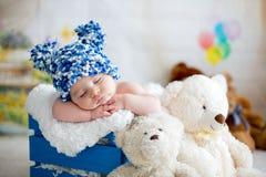 Behandla som ett barn lite pojken med den stack hatten som sover med den gulliga nallebjörnen Royaltyfria Bilder