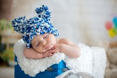 Behandla som ett barn lite pojken med den stack hatten som sover med den gulliga nallebjörnen Arkivbilder