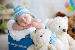 Behandla som ett barn lite pojken med den stack hatten som sover med den gulliga nallebjörnen Arkivfoton