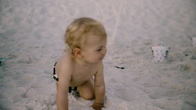 Behandla som ett barn lite pojken med en leksakkrypning på stranden Royaltyfria Foton